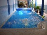 Beltéri, feszített víztükrű üvegmozaik burkolatú vasbeton úszómedence